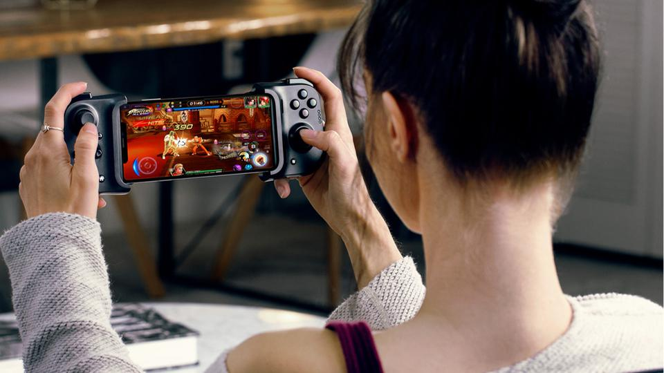 Woman playing Street Fighter with iPhone in Kishi controller