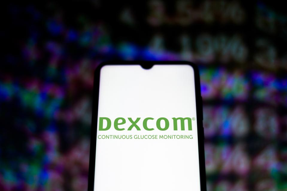In this photo illustration the DexCom logo seen displayed on...