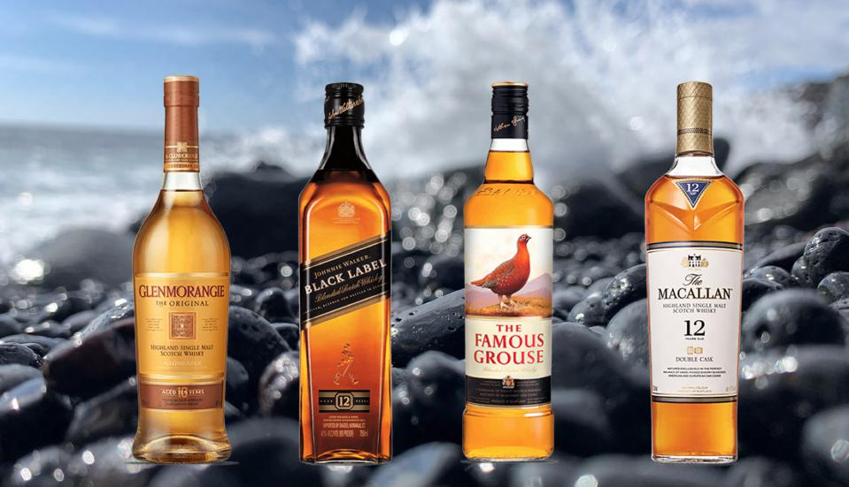 Four bottles of scotch lined up in front of a cresting wave on a black pebble beach.
