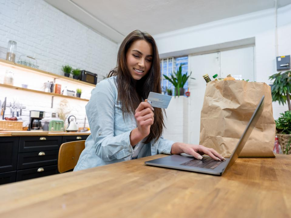 Woman grocery shopping online paying by credit card