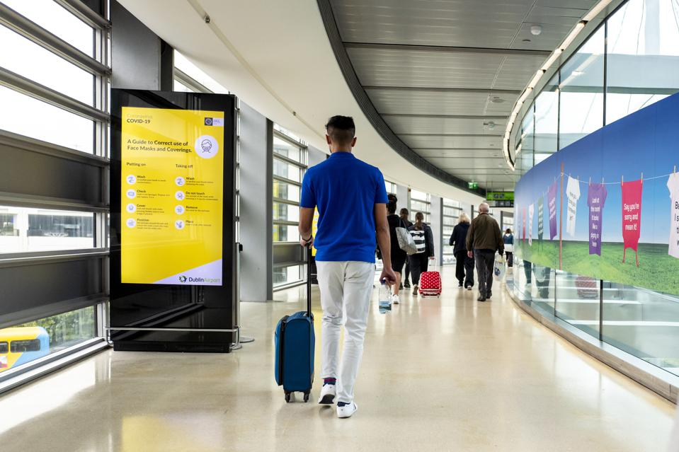 Passengers walks past Covid-19 signage arriving at Dublin Airport, Ireland EU Europe