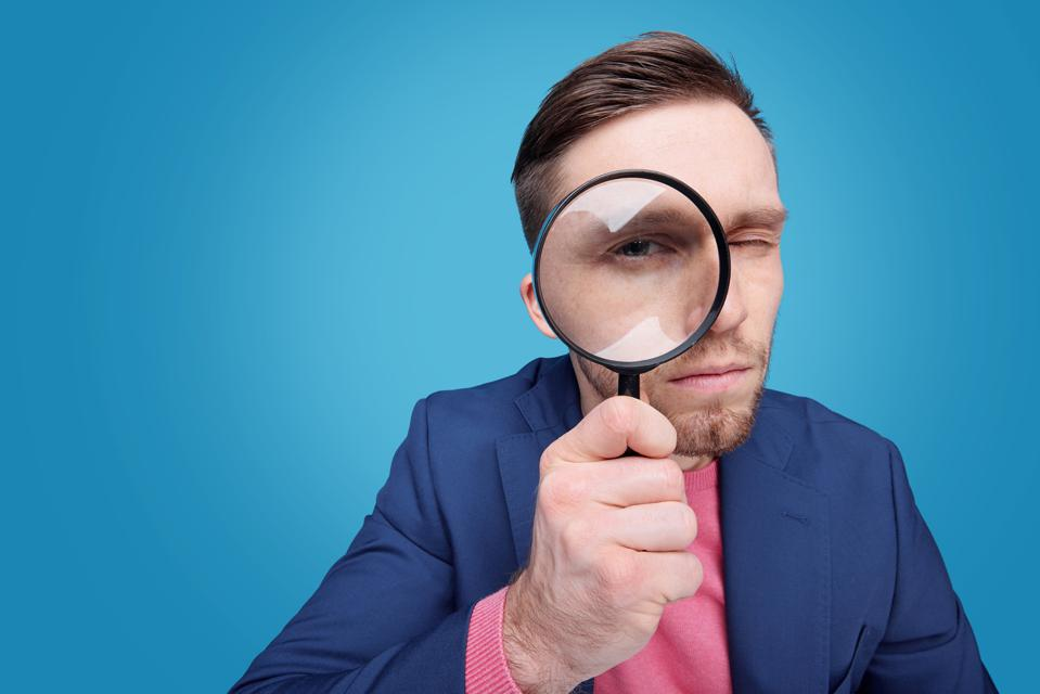 Serious young male detective holding magnifying glass by right eye