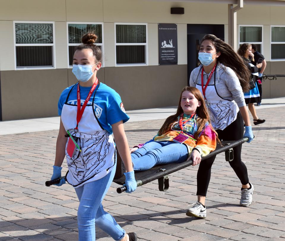 Two middle school students wearing medical masks carry a fellow student on a stretcher.