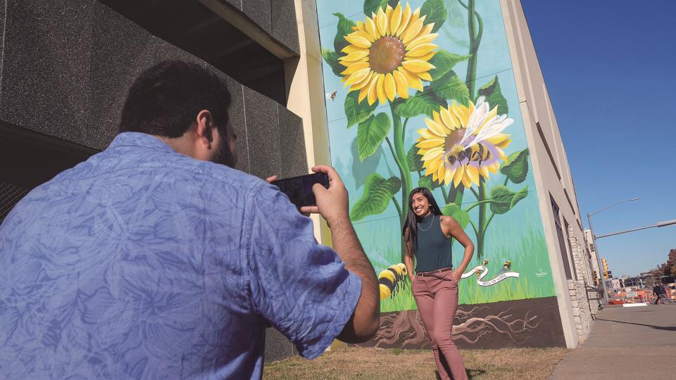 Couple taking a photo by a mural in Topeka Kansas