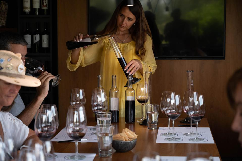 A winemaker measures wine during a blending session.