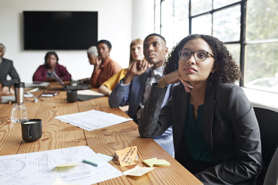 Businesswoman sitting by entrepreneurs in meeting