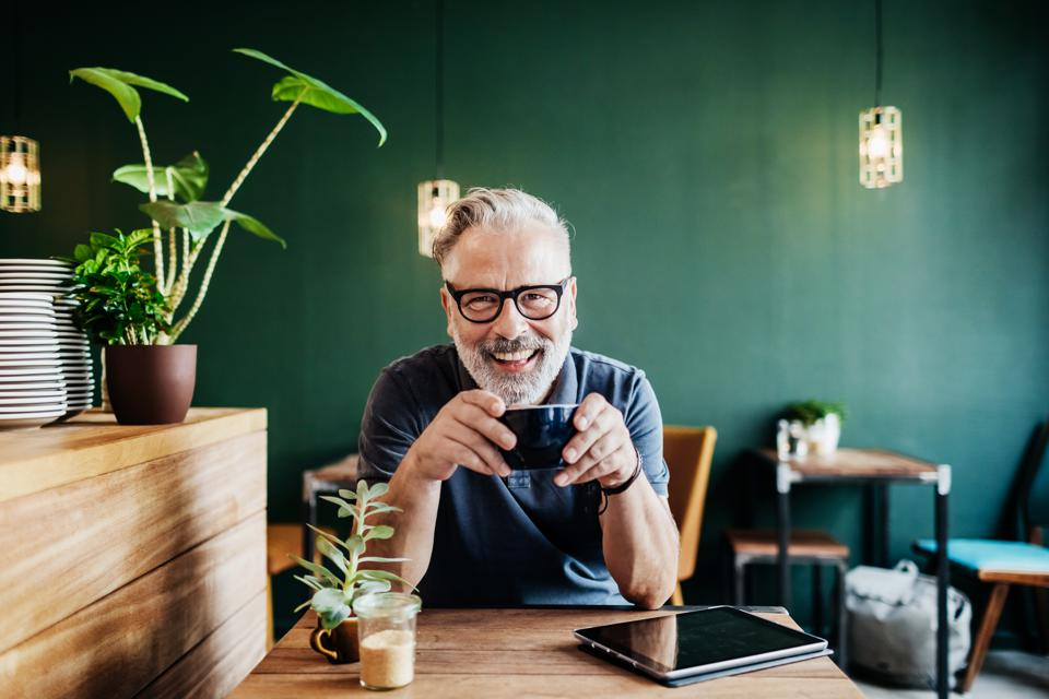 Portrait Of Cafe Customer Smiling While Drinking Coffee