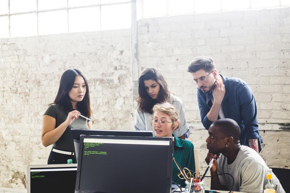Confident young professionals planning while coding in computer at workplace