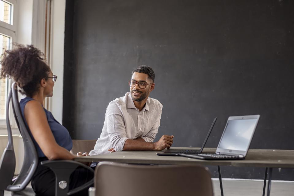 businessman looking at female manager in her modern office