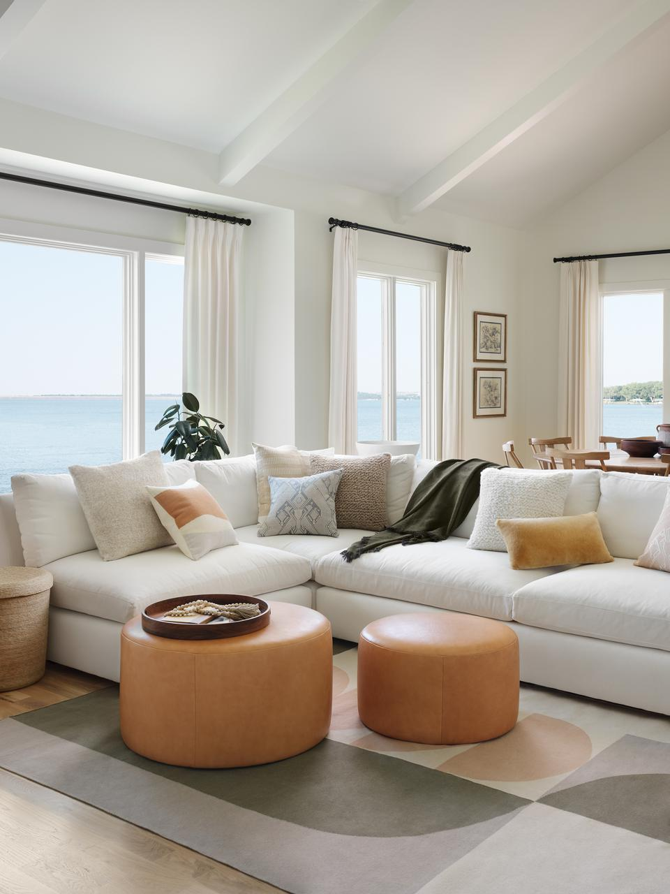 A living room space filled with The Citizenry's leather poufs, pillows and cotton rug.