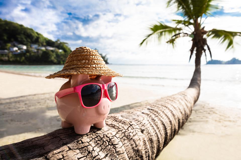 Pink Piggybank With Sunglasses On Tree Trunk At Beach