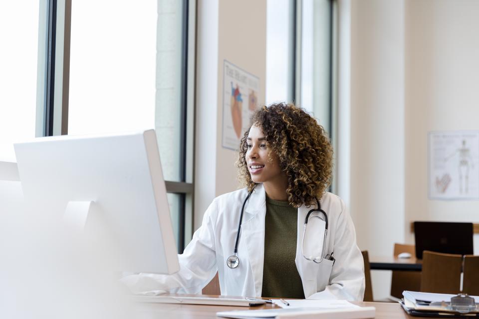 Mid adult female doctor reviews patient records on desktop PC
