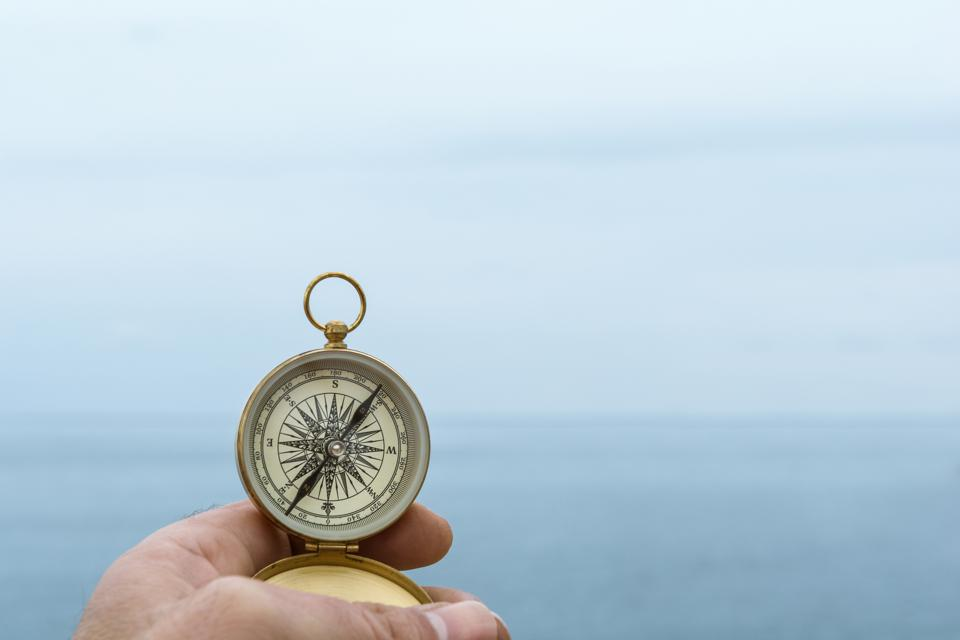 Compass held up over ocean to navigate rough water. Let's hope it isn't a 3-hour tour!