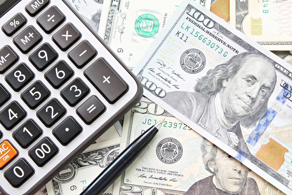 Top view or flat lay of calculator and pen on American Dollars cash money