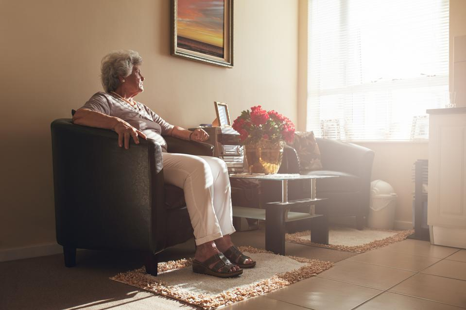 Senior woman sitting alone on a chair at home