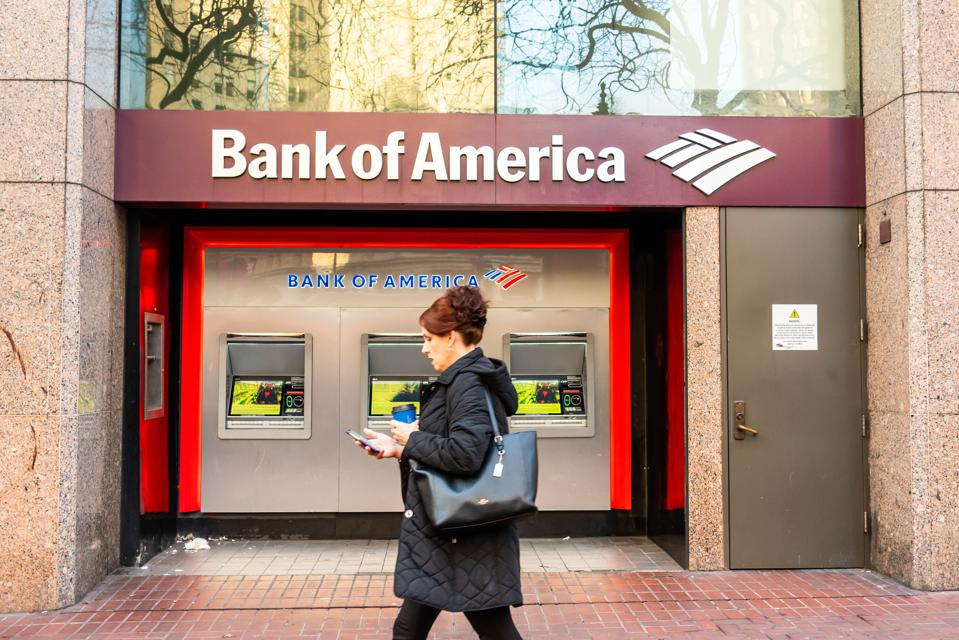 A pedestrian walks past Bank of America ATMs...