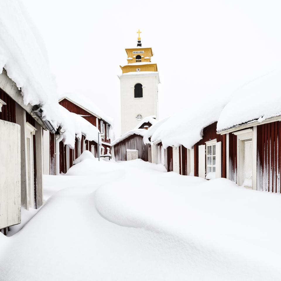 Wooden houses and the church of Gammelstad, near Luleå in northern Sweden, covered in snow.
