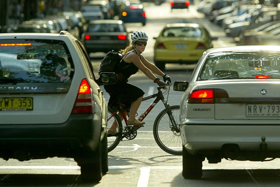 Cyclist, Monique Boggia, crosses an intersection in the city on her bike as cars