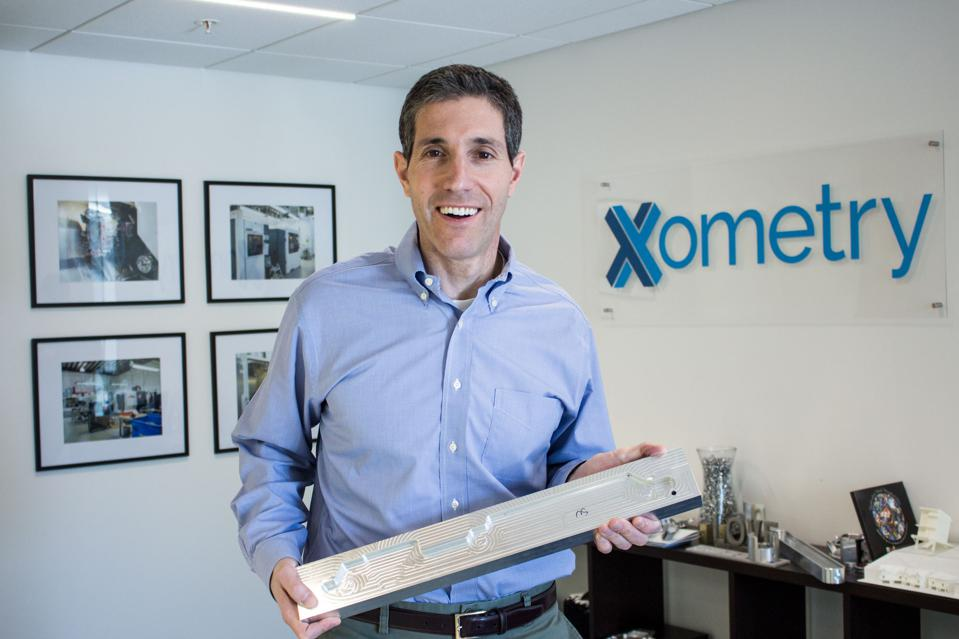 Xometry CEO Randy Altschuler holds a part in the Xometry office