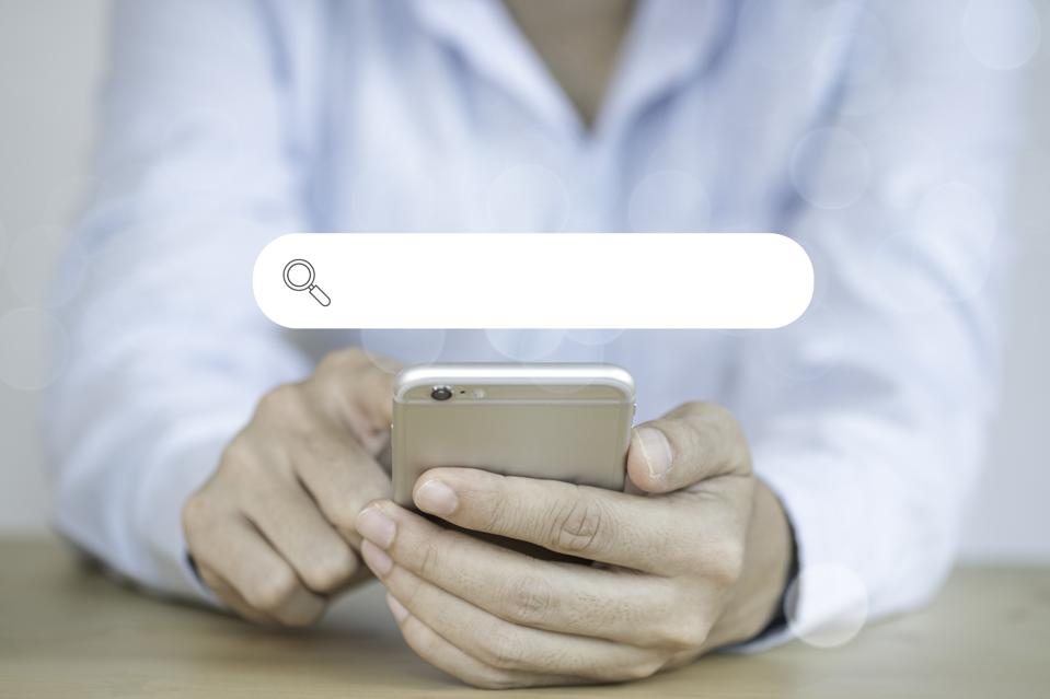 Midsection Of Woman Using Mobile Phone With Search Engine Symbol