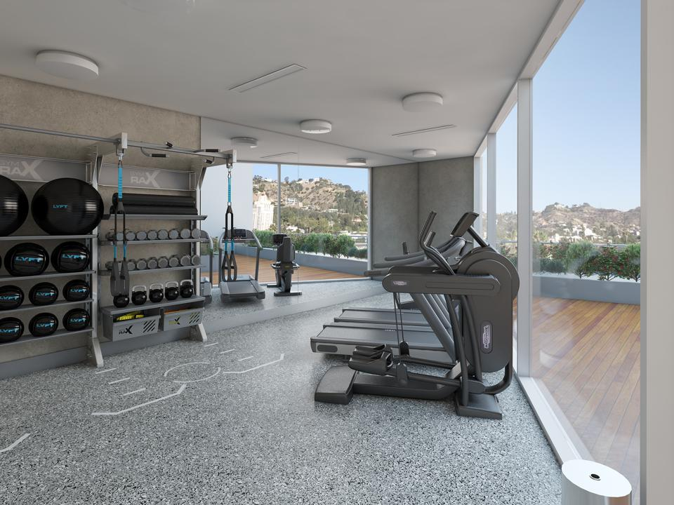 A home gym with floor-to-ceiling windows overlooking a beautiful mountainous view.