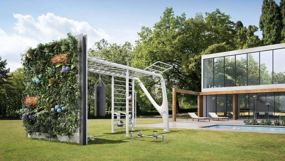 An outdoor home gym on a manicured lawn with a living wall.