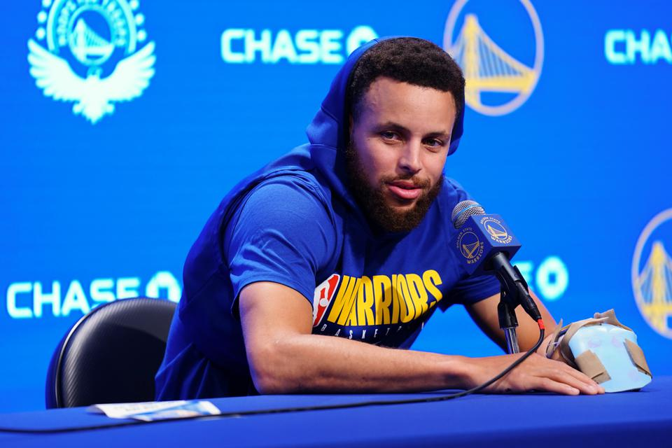 Golden State Warriors' Steph Curry at press conference seated with mic in blue hoodie.