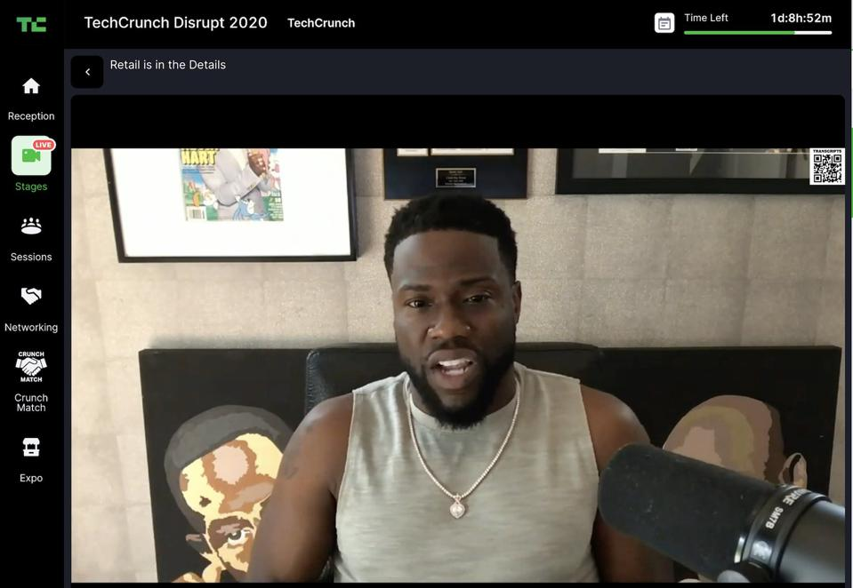 Actor Kevin Hart wearing a gray Fabletics tee shirt seated at a mic in his living room.