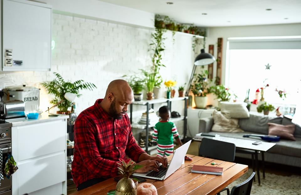 Father working from home on laptop and caring for son