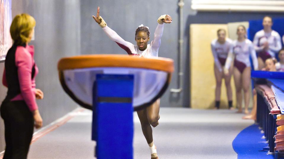Teammates and Coach Watch Tyra McKellar, a talented gymnast, Performing Vault