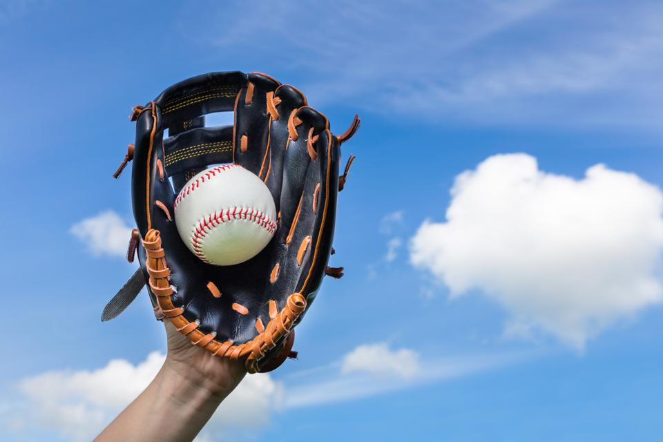Hand holding baseball in glove with blue sky