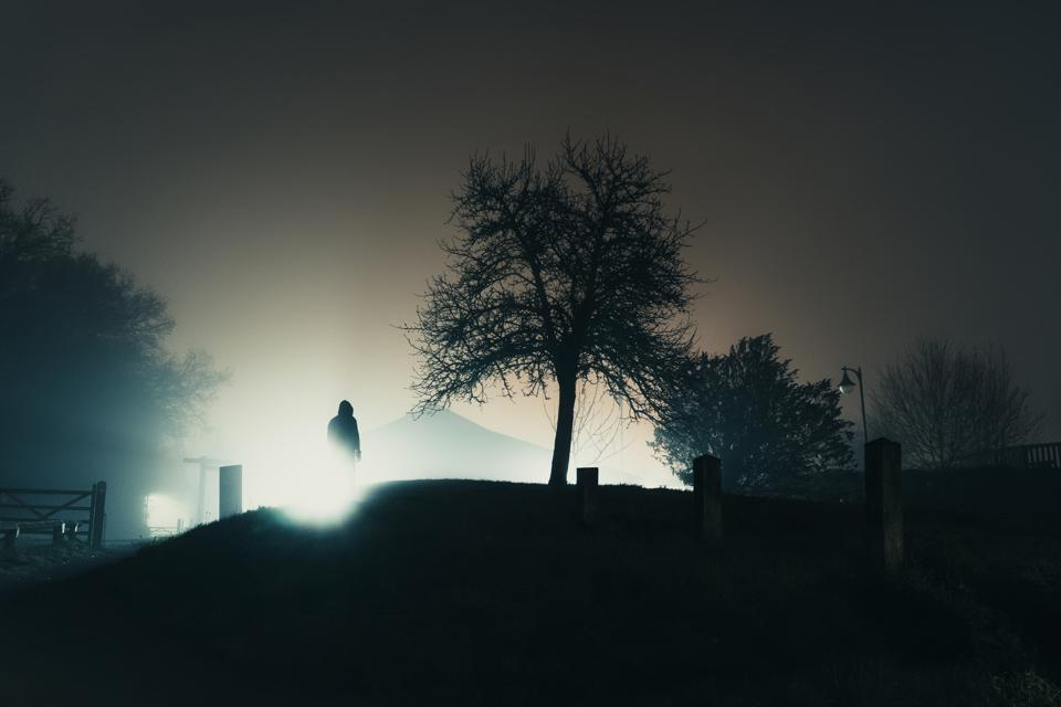 A hooded figure silhouetted against street lights next to a tree. On a mysterious misty, winters night