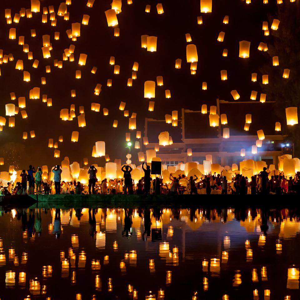 Beautiful image of a ceremony where lamps are lit and they rise to the heavens.