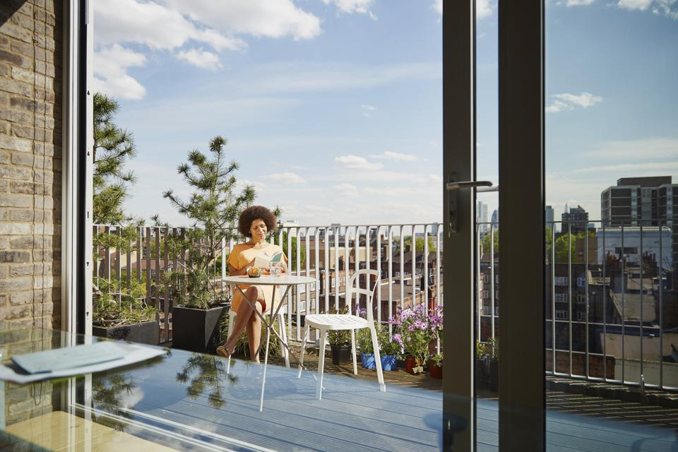 Woman sitting on balcony of apartment