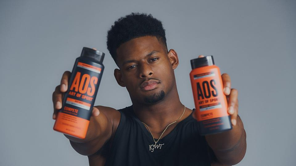 Juju Smith-Schuster, NFL wide receiver, holding bottles of Art of Sport body products in his hands.