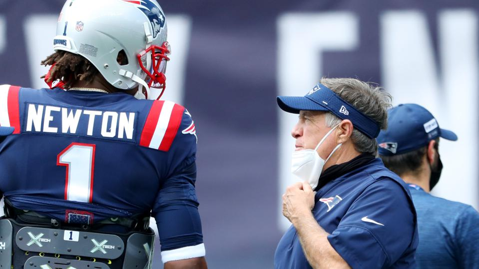 Head coach Bill Belichick of the New England Patriots talks with Cam Newton.
