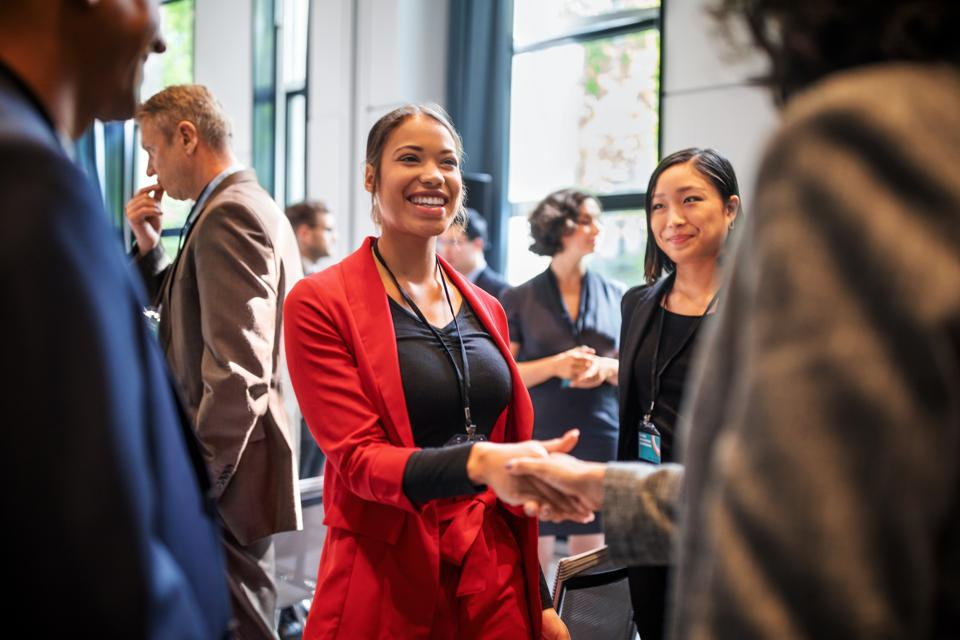 Business woman shaking hands at networking event.