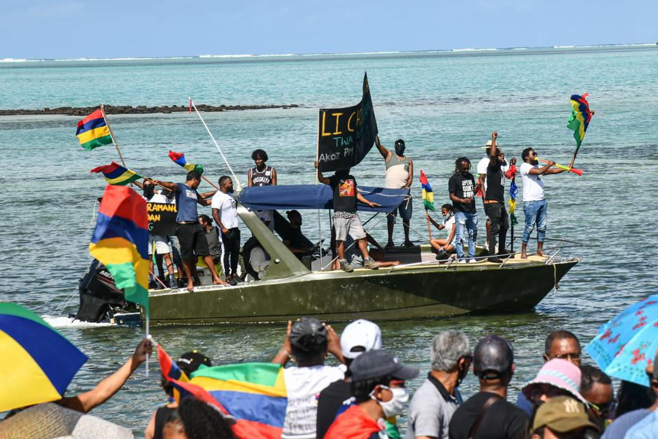 12 September: protesters hold a banner and Mauritius' national flags on a motorboat as they take part in a demonstration calling for the government to resign over the oil spill.  The Government has suppressed protestors since then.