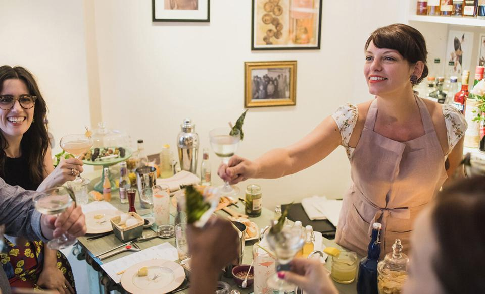 A party host serves a chilled martini to a guest around a plate of oysters