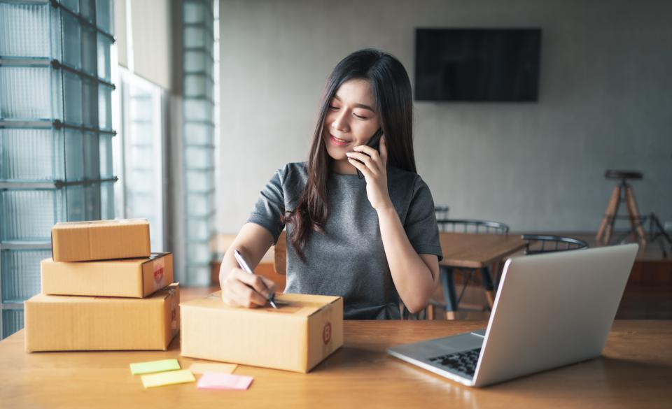 Young business woman working selling online. Entrepreneur owner using smartphone or laptop taking receive and checking online purchase shopping order to preparing pack product box. Packing goods for delivery to customer. E-commerce. Online Shopping
