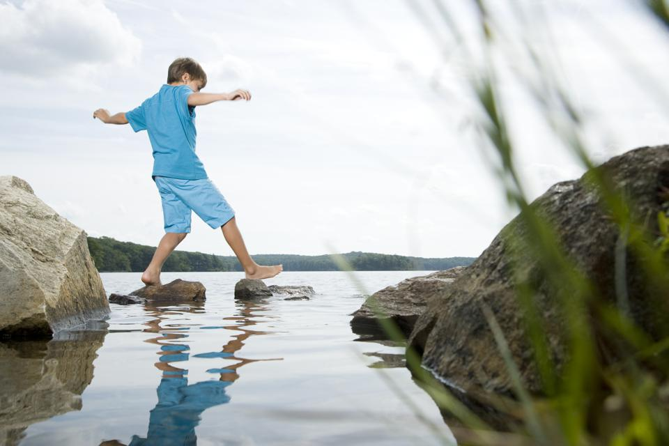 Boy walking barefoot across stones in lake showing small steps lead to career momentum