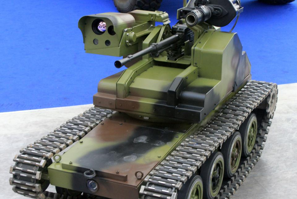 A tracked robot with a gun, a grenade launcher, and several cameras on a turret.