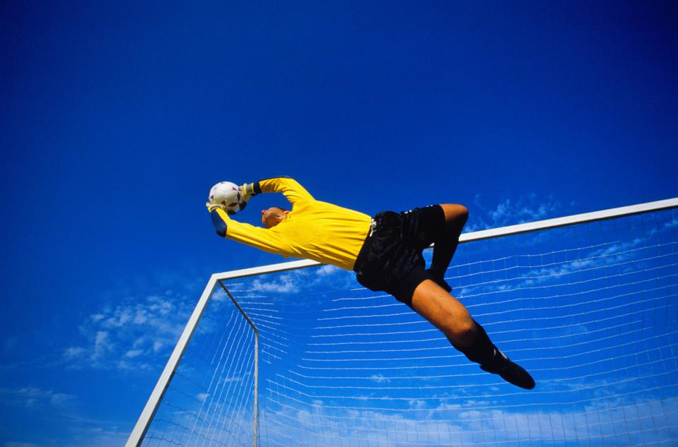 Football, goalkeeper in mid jump, goal in background, low angle view