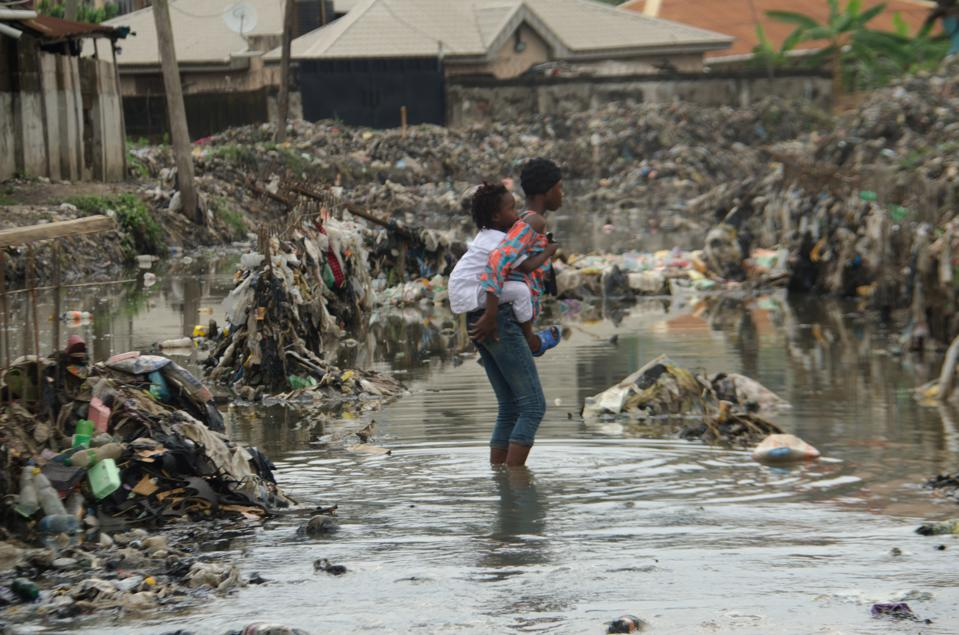 A girl carries her young brother as they walk through a filthy, flooded canal in Lagos.