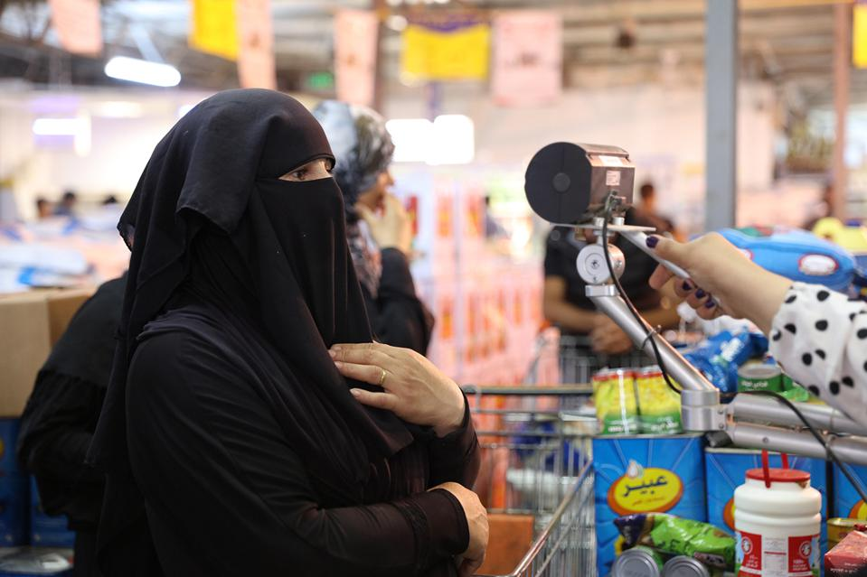 A Syrian woman in a black niqāb has her iris scanned to pay for food.