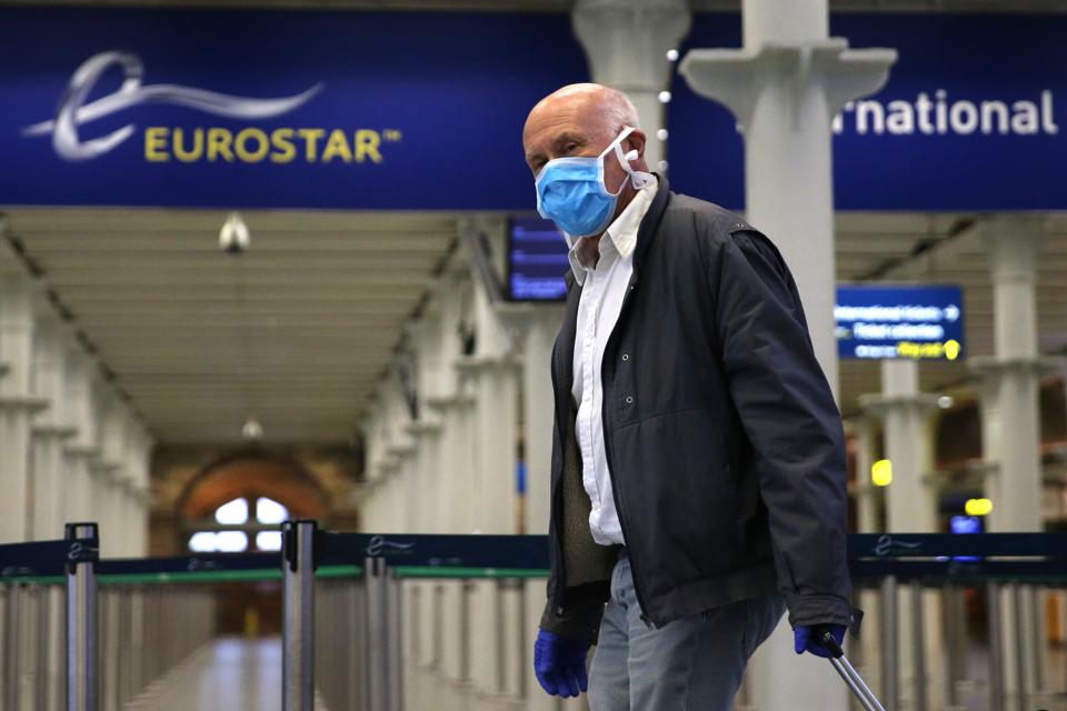 A passenger wearing a face mask arrives at the Eurostar terminal at St Pancras station in London