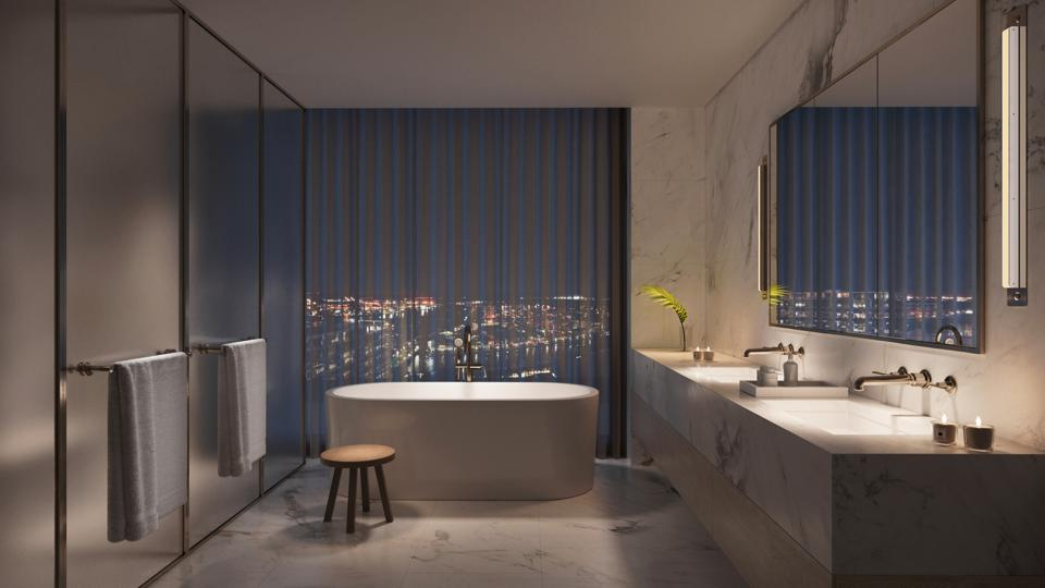 A bathroom with a deep soaking tub, marble accents and floor-to-ceiling windows.