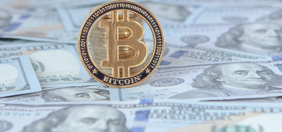 Bitcoin against the background of dollar bills. exchange bitcoin for dollars. fall of bitcoin