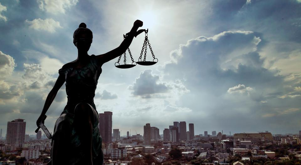 Picture of a female statue with the scales of justice in front of a cityscape