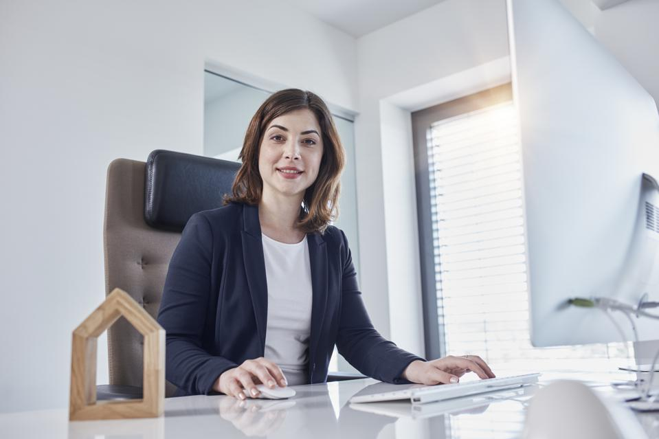 Portrait of smiling young businesswoman at desk in office with architectural model